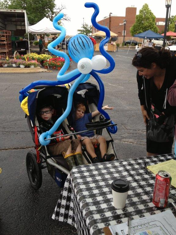 Two boys in a stroller with an octopus balloon placed over them